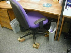 Office chair with wheels replaced by rocks.
